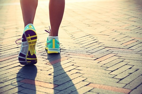 woman feet running on street in running shoes