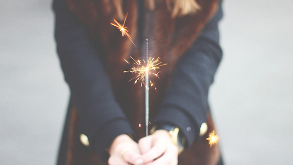 woman holds candle for new years celebration